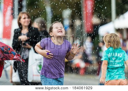 RIGA LATVIA - AUGUST 17 2014: People on the streets of Riga City Festival. Children are happy with water attractions.