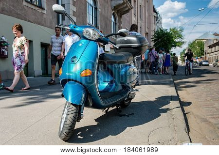 RIGA LATVIA - MAY 24 2014: Miera street Pentecost. Side of the street stands scooter. People walking down the street.