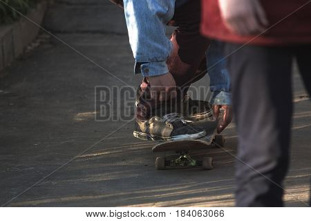 Skater Rides On A Skateboard In Old Ragged Sneakers