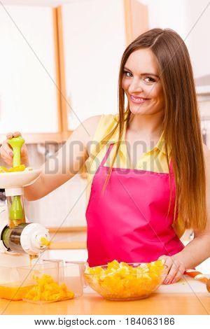 Woman Making Orange Juice In Juicer Machine