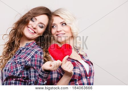 Generation relationship mother's day concept. Adult daughter and mother posing with red heart shape love symbol. Two cheerful casual style women