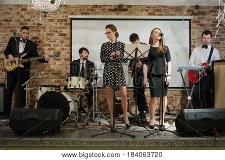 Music band of six people (two women, four men) performs on stage in club
