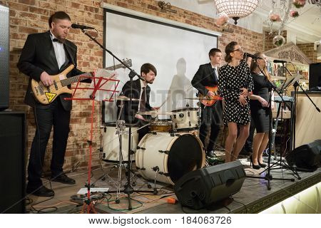 Music band of six young people (two women, four men) performs on stage in club