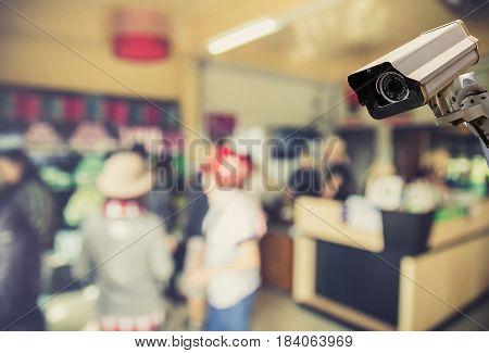 Image of CCTV security camera on blurred coffee shop background. vintage filter effect