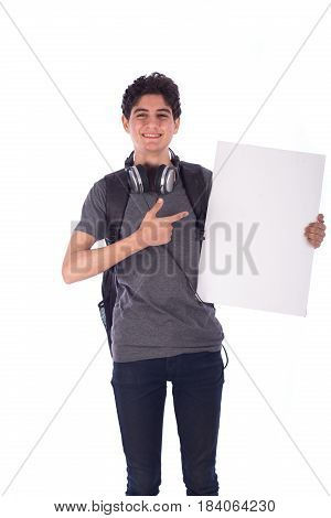 Portrait of smiley happy friendly young student holding an empty blank board and pointing to it teenager wearing gray t-shirt and jeans with a headphone and back-bag isolated on white background