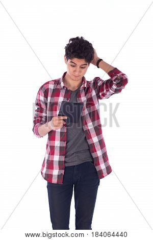 Portrait of confused teenage boy holding his head and looking to the tablet teenager wearing open red shirt and gray t-shirt and jeans isolated on white background