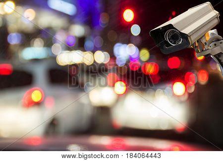 Image of CCTV security camera on blurred night street background. vintage filter effect
