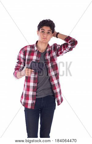 Portrait of puzzled teenage boy holding his head and a tablet by the other hand teenager wearing open red shirt and gray t-shirt and jeans isolated on white background