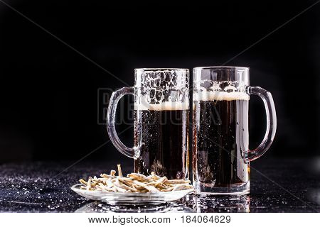 Two mugs of beer, anchovies on empty black background