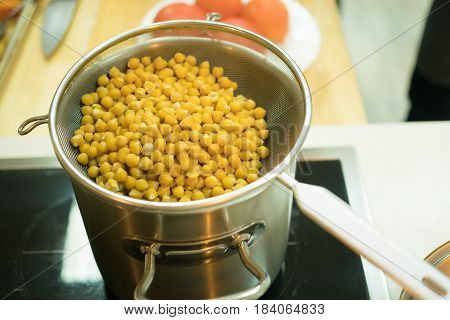 Photo of cooked peas on stove in kitchen