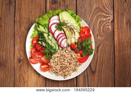 buddha bowl with mixture of vegetables quinoa on wooden background