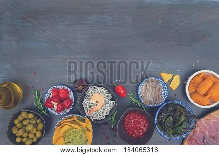 Table with spanish tapas - anchovies with peppers padron, jamon, croquetes, guacamole and olives, border with copy space, picnic table, retro toned