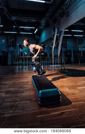 Man Doing Step Up Jumps In Health Club
