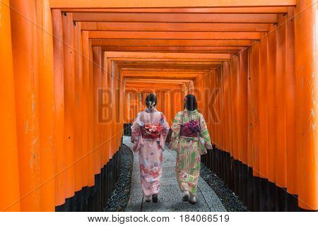 Two geishas among red wooden Tori Gate at Fushimi Inari Shrine in Kyoto Japan. Women wearing traditional japanese kimono in Kyoto Japan.