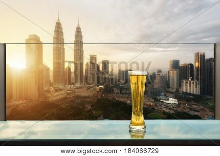 Beer and foam beer on table in rooftop bar with Kuala Lumpur skyscraper in background in Kuala Lumpur Malaysia.