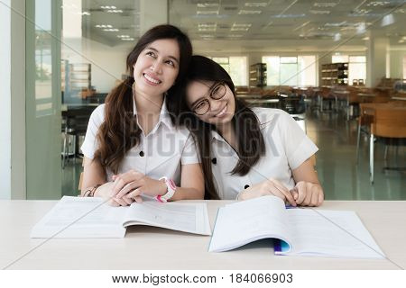 Asian two smiling student girl in the library studying and day dreaming. Asian student thinking with hand on chin and looking up education and future concept.