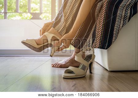 Woman taking off high heels shoes at home