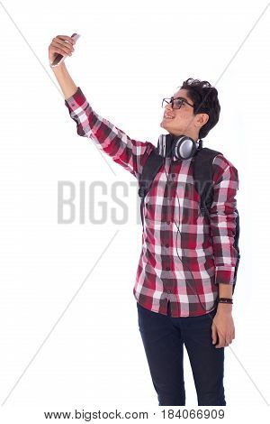 Portrait of smiley happy friendly young student taking selfie and looking side teenager wearing red shirt and jeans with a headphones and back-bag isolated on white background