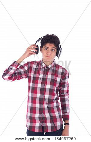 Portrait of smiley friendly teenage boy listening to music and holding the headphones teenager wearing red shirt and jeans isolated on white background