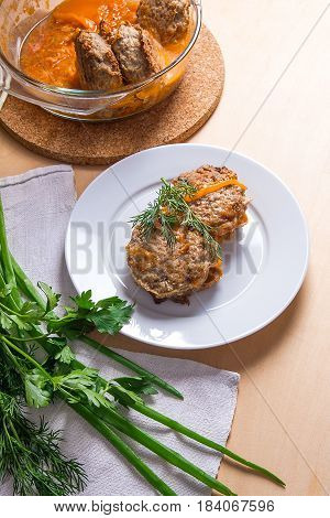 Rissole Of Pork Served On A White Plate And Herbs - Dill, Green Onion, Parsley Around The Plate.