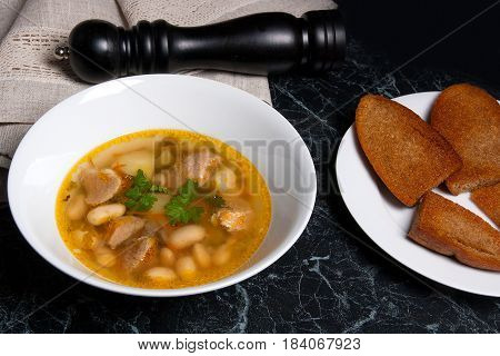 Bean Soup In White Plate, Several Toast On White Plate On A Black Stone Background.