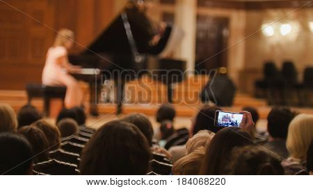 Spectators in concert hall during performing piano girl- people shooting performance on smartphone, telephoto