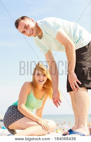 Help in relationship friendship love and trust concept. Man helping his girlfriend to get on fenece