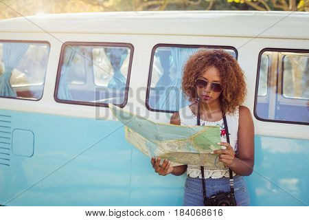 Woman leaning on campervan and looking at map on a sunny day