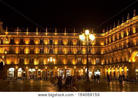 SALAMANCA, SPAIN - MAR 29, 2017: Pedestrians stroll in the Plaza Mayor at night.