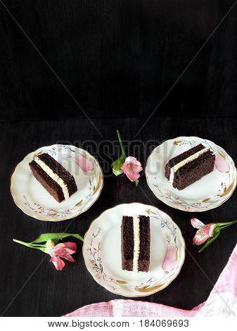 A composition made of three cakes on the plates surrounded by flowers