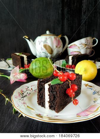 A composition made of three cakes on the plates surrounded by flowers, lemons, berries and the tea set