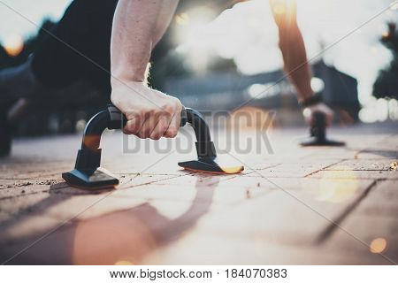Healthy lifestyle concept.Training outdoors.Handsome sport man doing pushups in the park on the sunny morning. Blurred background. Horizontal closeup