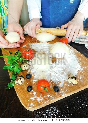 Yeast dough and bakers forming dough surrounded by tomatoes, fresh green, quail eggs and olives
