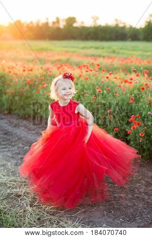 girl model, childhood, fashion and summer concept - happiness of a little blonde in a bright red holiday dress and headband, she's at the field edge with blossoming poppies and look into the distance