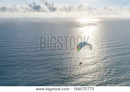 Silhouette flying tandem paragliders over the sea at sunset.
