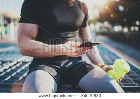 Muscular handsome athlete checking burned calories on smartphone application and smart watch after good workout session on city park in the sunny morning.Blurred background
