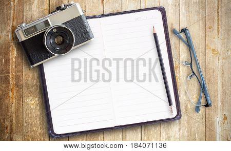 Old vintage camera and photo papernotebook with glasses on wooden table. Top view with copy space for design