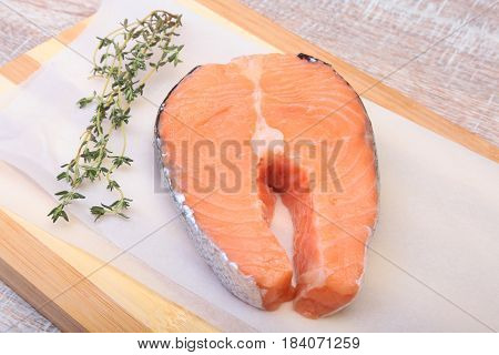fresh raw salmon with spices on wooden cutting board. ready for cookin.