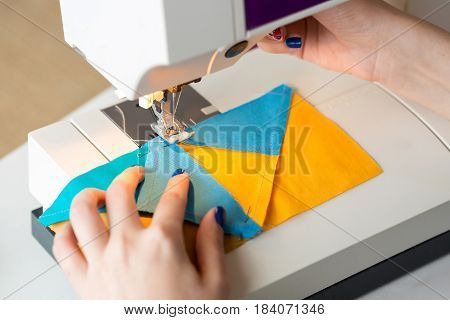 needlework and quilting in the workshop of a tailor - close-up on hands of a tailor woman working on sewing machine and stitching pieces of blue and yellow fabric