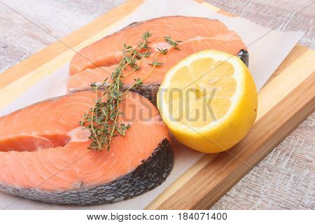 fresh raw salmon with spices and lemon on wooden cutting board. ready for cookin.