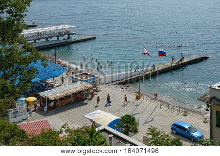 GASPRA, CRIMEA, RUSSIA - AUGUST 29: Summer sun is illuminating beach embankment and vacationers on it on August 29, 2016 in spa resort Gaspra in Crimea, Russia.