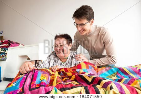 needlework and quilting at the workshop of a tailor woman - a tailor stitches brightly colored quilt on the sewing machine, standing behind her man with a smile hugged the woman master