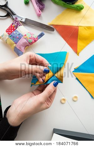 needlework and quilting in the workshop of a tailor on white background - close-up on hands of a tailor holding scraps of fabrics lying on a white table with buttons, pin cushion, scissors