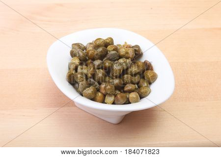 bowl with fresh capers on wooden table.