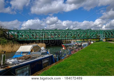 River Lea near Bow with longboats and railway bridge in Spring.