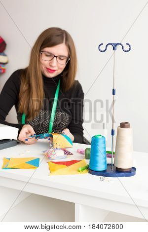 needlework and hand quilting in the workshop of a young tailor - young tailor woman in glasses at work with pieces of colored cloth on the table with threads, fabrics, needles vertical