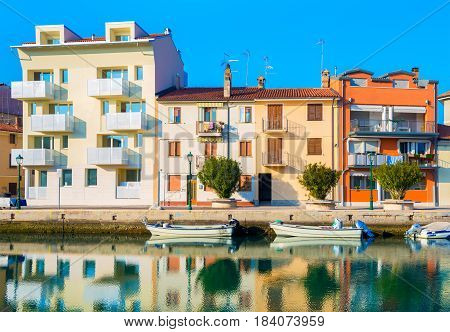 Grado - December 2015, Italy: Colored houses and boats on the water one of the canals in Grado