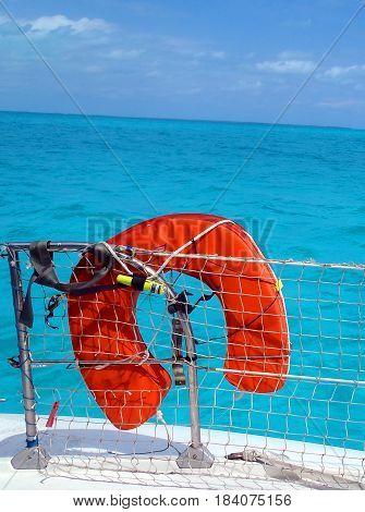 Orange life preserver over a turquoise blue sea