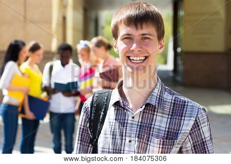 Portrait of college boy holding books with blurred students