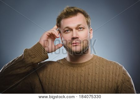 doubt, expression and people concept - man thinking over gray background.